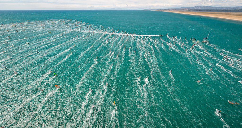 風下から風上へ、疾走してゆくボートの航跡がラビットスタートのスタートライン。沖にセイフティブイが設置され、ビーチとその間がレースエリアになる。